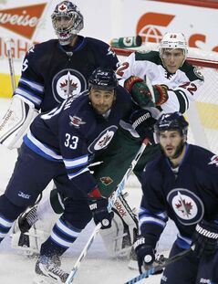 The Winnipeg Jets' Dustin Byfuglien (33) and the Minnesota Wild's Nino Niederreiter (22) fight for position in front of Jets' goaltender Al Montoya (35) Thursday. A leaner, meaner Buff looks like he could be a force this year.