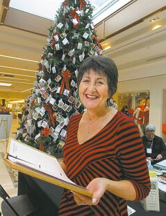 Pam Bolton, a Hospice and Palliative Care Manitoba volunteer, helps out at the organization's memory tree in St. Vital Centre. People can affix a card to the tree in memory of a loved one who has died.                    volunteers for Hospice and Palliative Care Manitoba in many different roles. She will be helping out at the HPCM Memory Tree this Thurs Dec 13th at the St. Vital Mall from 9:30 am to noon. Here she poses for a photo in front of the tree. The Hospice Memory Tree is a special place to help ease the pain of grief during the holiday season and where you are invited to hang a card of remembrance for your loved one who has died. The tree offers a very meaningful and symbolic way to remember loved ones over the holiday season. This service to the community is provided at no cost to anyone wishing to honour the memory of their loved one. Specially trained volunteers from Hospice & Palliative Care Manitoba are on hand at the Tree to offer support and information on bereavement services. December 13, 2012  BORIS MINKEVICH / WINNIPEG FREE PRESS