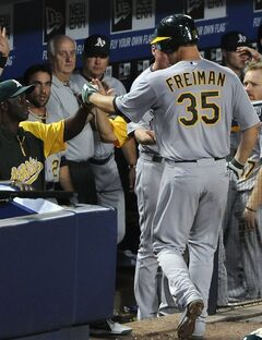 Oakland Athletics' Nate Freiman (35) is congratulated in the dugout after his solo home run against the Atlanta Braves during the seventh inning of a baseball game Sunday, Aug. 17, 2014, in Atlanta. (AP Photo/David Tulis)