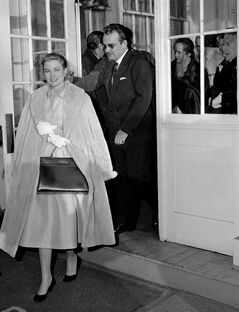 FILE - In this Jan. 5, 1956 file photo actress Grace Kelly sports a Hermes bag as she and Prince Rainier III of Monaco leave a luncheon party in Philadelphia where they announced their engagement. The status handbag market is driven by celebrity trendsetters such as, more recenlty, Katie Holmes and Victoria Beckham, and now some big auction houses are getting in on the act. The style of handbag favored by Kelly came to be known as a