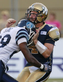 Blue Bombers quarterback Buck Pierce (4) gets hit late and hard by the Toronto Argonauts' Brandon Isaac (28) in Winnipeg on Saturday.