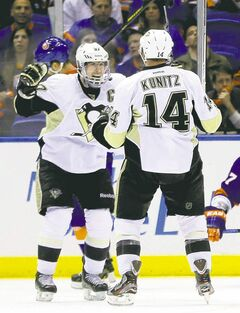 Chris Kunitz (14) celebrates his overtime goal with Penguins captain Sidney Crosby, who drew an assist on the play.