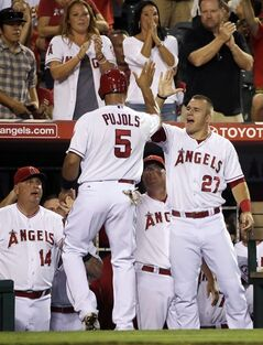 Spectators, top, applaud as Los Angeles Angels' Albert Pujols (5) high-fives teammate Mike Trout after scoring on a single hit by Erick Aybar during the fourth inning of a baseball game against the Oakland Athletics, Saturday, Aug. 30, 2014, in Anaheim, Calif. (AP Photo/Jae C. Hong)