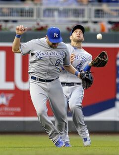 Kansas City Royals' Alex Gordon reaches for the popup off the bat of Minnesota Twins' Chris Parmelee as third baseman Mike Moustakas moves out of the way in the third inning of a baseball game, Tuesday, July 1, 2014, in Minneapolis. Gordon couldn't make the catch and Parmelee reached on the play on Gordon's error. (AP Photo/Jim Mone)