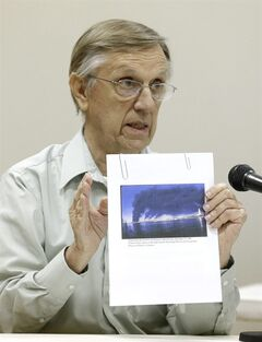 William Fontenot of the Sierra Club in Louisiana shows a photo he took of a 1989 explosion at an Exxon Refinery in Baton Rouge at an Environmental Protection Agency public hearing, Tuesday, Aug. 5, 2014, in Galena Park, Texas. The EPA is considering a rule that would force refineries to monitor emissions of benzene. (AP Photo/Pat Sullivan)