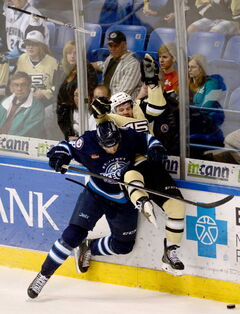 Scranton Penguins' Bobby Farnham loses his stick as he takes a hard hit from St. John's IceCaps' Ben Chiarot during an AHL hockey Eastern Conference finals playoff game Thursday in Wilkes-Barre, Pa.