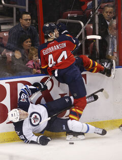 Florida's Erik Gudbranson rocks Winnipeg blue-liner Toby Enstrom during second-period action in Sunrise, Fla., Thursday.