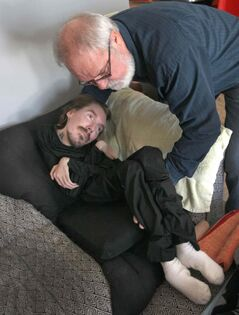 Home-care client Tom Landy gets help from his dad, Ed.