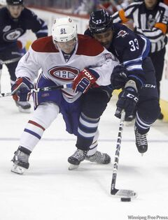 Jets blue-liner Dustin Byfuglien (33) battles for the puck with Hab Raphael Diaz during second-period action.