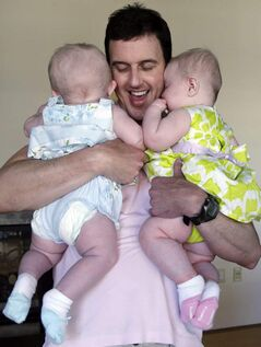 Trey Powell with his twin six-month-old daughters, born via a surrogate.
