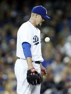 Los Angeles Dodgers starting pitcher Paul Maholm tosses the ball after giving up a two-run home run to San Francisco Giants' Brandon Crawford to score Brandon Hicks during the fifth inning of a baseball game, Friday, May 9, 2014, in Los Angeles. (AP Photo/Danny Moloshok)