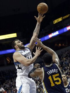 Minnesota Timberwolves' Nikola Pekovic, left, of Montenegro, shoots over Utah Jazz's Derrick Favors in the second half of an NBA basketball game, Saturday, Jan. 18, 2014, in Minneapolis. Pekovic led the Timberwolves with 27 points and 14 rebounds in their 98-72 win. (AP Photo/Jim Mone)