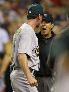 Oakland Athletics manager Bob Melvin, left, argues with home plate umpire James Hoye, right, as they leave the field after Athletics' Nick Punto was called out on strikes to end the baseball game against the Seattle Mariners in the ninth inning on Friday, July 11, 2014, in Seattle. (AP Photo/Ted S. Warren)