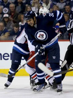 Winnipeg Jets' Dustin Byfuglien (33) tries to get out of the way of a point shot during second period NHL hockey action against the Columbus Blue Jackets' at MTS Centre in Winnipeg, Saturday, January 11, 2014. (TREVOR HAGAN/WINNIPEG FREE PRESS)