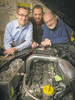 Prof. Sage Kokjohn (from left), researcher Derek Splitter and Prof. Rolf Reitz show off an engine that mixes diesel with gasoline.