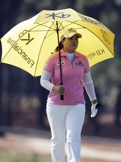 Inbee Park, of South Korea, uses an umbrella to avoid the heat as she walks down the 13th hole during the first round of the U.S. Women's Open golf tournament in Pinehurst, N.C., Thursday, June 19, 2014. (AP Photo/Bob Leverone)