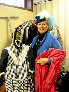 Margaret Mills, costume mistress for the Headingley United Church Players, shows off two of the costumes that will be in a liquidation sale on Oct. 18 and 19 at Headingley United Church.