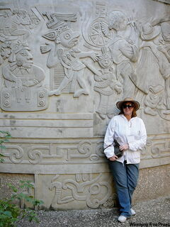 Visitor stands next to carvings depicting Totonac life.