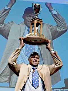 St. Francis Xavier linebacker Henoc Muamba hoists the President's Trophy as the nation's top defensive player.