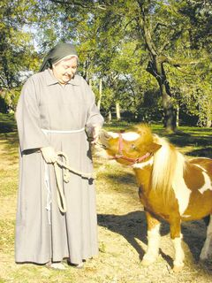 Sister Angela Chandler shows off one of the 80 miniature horses stabled at the Monastery of St. Clare.