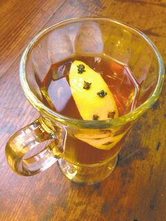 This spirited remedy for the common cold includes a dash of whiskey (optional), chamomile honey, garden-infused simple syrup (see recipe) to taste, hot water, and a lemon studded with cloves.