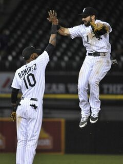 Chicago White Sox's Adam Eaton (1) and Alexei Ramirez (10) celebrate after defeating the Detroit Tigers 8-2 in a baseball game in Chicago, Wednesday, June 11, 2014. (AP Photo/Paul Beaty)