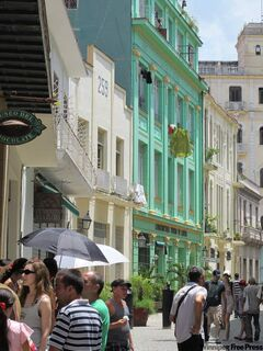 A brightly-colored building rises over a street in Havana.