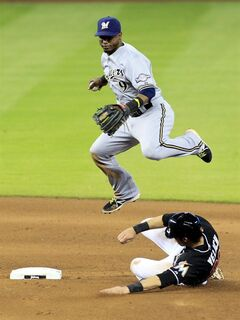 Miami Marlins' Christian Yelich, bottom, is out as he slides as Milwaukee Brewers shortstop Jean Segura leaps in the seventh inning of a baseball game in Miami, Saturday, May 24, 2014. (AP Photo/Joe Skipper)