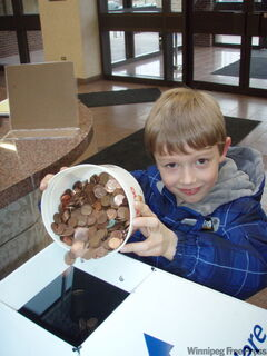 Paul Houston, 7, dumps coins for Pennies from Heaven into bin at the Free Press.