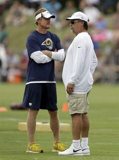 St. Louis Rams head coach Jeff Fisher, right, talks with Rams general manager Les Snead during training camp at the NFL football team's practice facility on Saturday, July 26, 2014, in St. Louis. (AP Photo/Jeff Roberson)