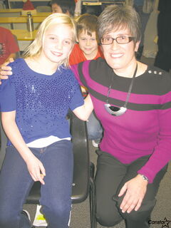 Sydney Stefanson sits with her teacher, Mary-Ann Mitchler who wears the microphone around her neck.