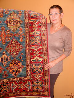 Gwen Repeta poses with one of the rugs that will be for sale at Ten Thousand Village's rug sale.