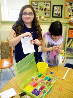 Victory School students making loom bracelets.