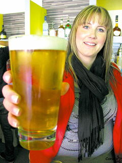 General manager Claudette Paradis holds a pint of The Hub's specialty lager.