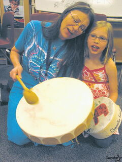 Val Vint (left) and Payton Lang take part in a Dream Catchers Club drumming session at Chancellor School.