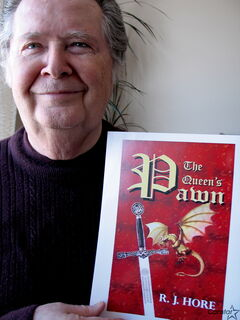Ron Hore shows off the cover of his new medeival fantasy, The Queen`s Pawn.