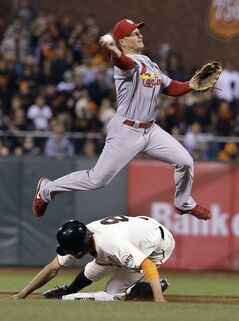 St. Louis Cardinals second baseman Mark Ellis attempts a double play after San Francisco Giants' Hunter Pence is forced out at second base in the ninth inning of a baseball game Wednesday, July 2, 2014, in San Francisco. The Giants' Buster Posey was safe at first base on the play. St. Louis won the game 2-0. (AP Photo/Eric Risberg)