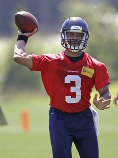 Seattle Seahawks quarterback Russell Wilson passes at an NFL organized team activity football practice Monday, June 2, 2014, in Renton, Wash. (AP Photo/Elaine Thompson)