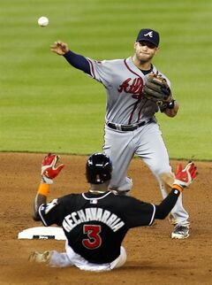 Atlanta Braves second baseman Tommy La Stella, top, tags out Miami Marlins' Adeiny Hechavarria while turning a double play catching Marlins' Jeff Baker in the fifth inning during a baseball game in Miami, Saturday, May 31, 2014. (AP Photo/Joe Skipper)