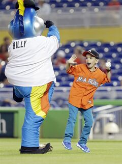 Miami Marlins fan Jonathan Esponda, right, dances with Marlins' mascot