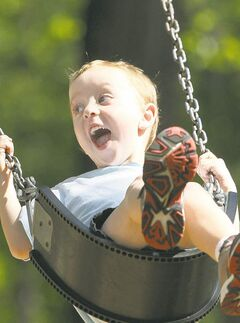 Asher Rohne, 4, has a ball during a swing ride at Kildonan Park Monday.