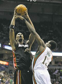 Miami Heat's Chris Bosh shoots over Milwaukee's Ekpe Udoh Saturday.