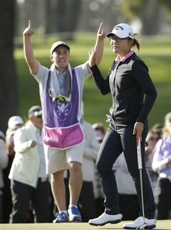 Lydia Ko of New Zealand reacts on the 18th green of the Lake Merced Golf Club after winning the Swinging Skirts LPGA Classic golf tournament on Sunday, April 27, 2014, in Daly City, Calif. Ko won the event after shooting a 3-under-par 69 to finish at 12-under-par. At left is her caddie Domingo Jojola. (AP Photo/Eric Risberg)