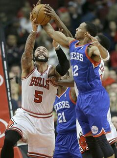 Chicago Bulls forward Carlos Boozer (5) battles for a rebound against Philadelphia 76ers forward Evan Turner (12) during the first half of an NBA basketball game in Chicago, Saturday, Jan. 18, 2014. (AP Photo/Nam Y. Huh)