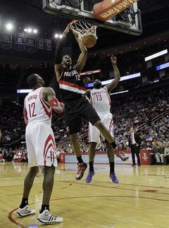 Portland Trail Blazers forward LaMarcus Aldridge (12) dunks between Houston Rocket's Dwight Howard (12) and James Harden (13) during the first half of an NBA basketball game, Monday, Jan. 20, 2014, in Houston. (AP Photo/Bob Levey)