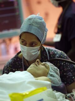 Anesthesiologist Fabienne Roelarts, left, hypnotizes patient Christel Place prior to her thyroid surgery in the operating theater of the Cliniques Universitaires St. Luc Hospital in Brussels on Friday, July 15, 2011. At the hospital, one third of all surgeries to remove thyroids and one quarter of all breast cancer surgeries are performed using hypnosis and local anesthetic rather than full anesthesia. (AP Photo/Virginia Mayo)