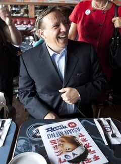 Coalition Avenir Quebec leader Francois Legault smiles as he sits in front of an Asian menu at a sports bar in Quebec City, Tuesday, August 14, 2012. Quebecers are going to the polls on Sept. 4. THE CANADIAN PRESS/Jacques Boissinot