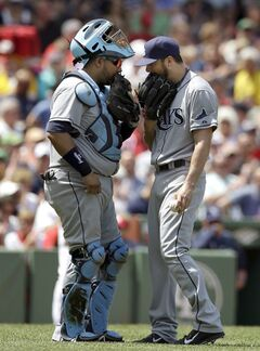 Tampa Bay Rays catcher Jose Molina, left, and pitcher Erik Bedard, right, hold their gloves over their mouths while speaking in the first inning of a baseball game against the Boston Red Sox, Sunday, June 1, 2014, in Boston. The Red Sox won 4-0. (AP Photo/Steven Senne)
