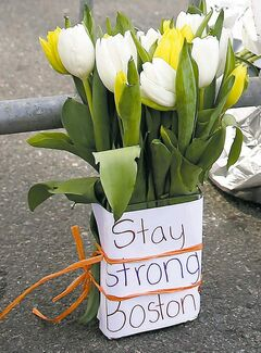 Flowers sit at a police barrier near the finish line of the Boston Marathon in Boston.