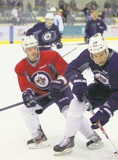 Defenceman Ian White (left) battles Patrice Cormier for the puck on the opening day of training camp Thursday.